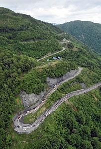 新緑がきれいな山肌の脇を抜け、半年ぶりに開通した山岳道路「白山スーパー林道」=白川村で、本社ヘリ「わかづる」から<br />
